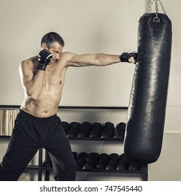 An image of a middle age man at the punch bag