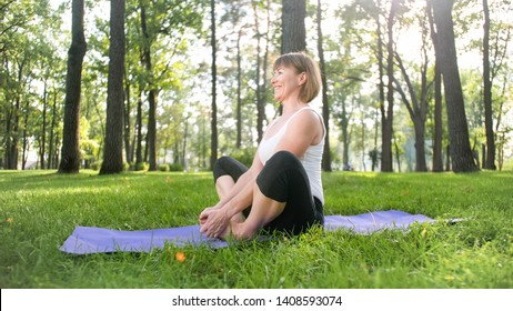 Image of middle aged woman practicing yoga or fitness on fresh green grass at park. Female physical and mental health. Person in meditation and harmony pf body and soul