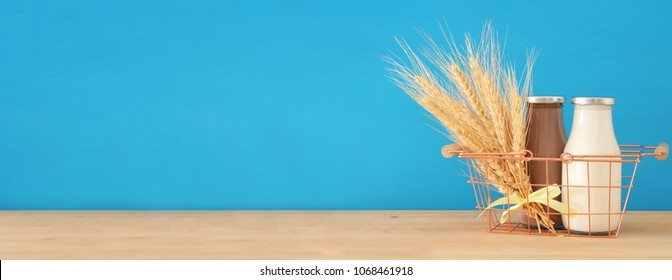 image of milk and Chocolate in the basket with wheat over wooden table and pastel background. Symbols of jewish holiday - Shavuot.