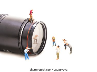 image of mini figure dolls photographer take picture on big DSLR lens isolated on white background.