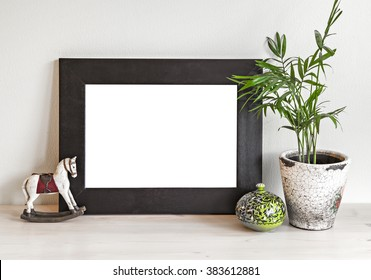 Image of a mockup scene with wooden frame, toy horse and plant pot.