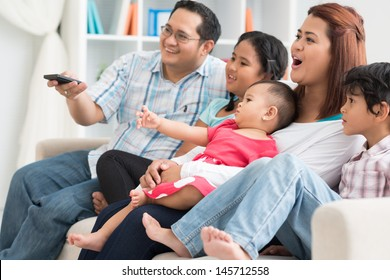 Image of a modern family watching TV at home