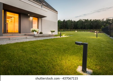 Image of modern villa with garden and decorative outdoor lighting, external view