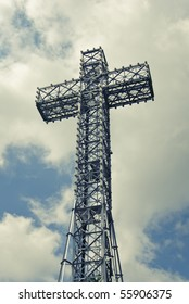 An image of Mont Royal Cross against sky with some clouds situated on the peak of the hill in Montreal, Quebec, Canada.