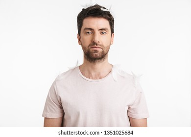 Image of morning man 30s with bristle in casual t-shirt standing under falling feathers isolated over white background