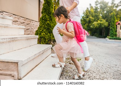 Image of mother and pupil daughter going back at home from kindergarten. Good relationship. Happy cute little girl with her mom feel happy after the preschool day, climb up the stairs at home outside