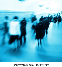 Image of motion blurred people walking in subway station.