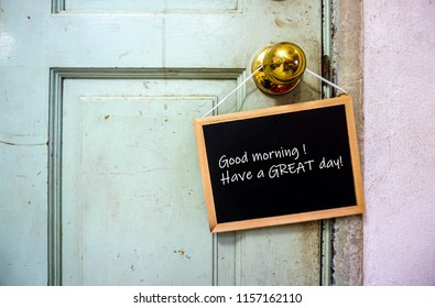 Image of motivational greeting good morning have a great day on mini notice board hanging on knob of old green door. Selective focus on notice board. Others in gradient blur.