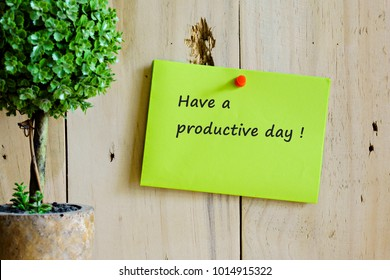 Image of motivational greeting have a productive day! on green note push-pinned on wooden wall. Besides a decorative green plant in vase. Selective focus on notice board. Others in gradient blur.