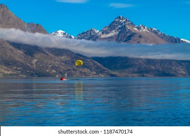 image of mountain partly covered in clouds with snow and lake with water surface reflection and boat with para sailer and mountains and blue sky in background