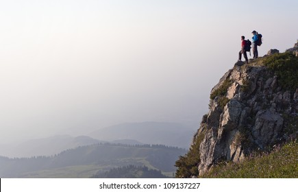 Image of mountain scenery, on top of which stands the silhouette of a tourist couple, who enjoys success achieved heavy climbing.