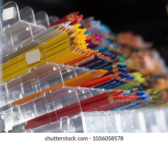 Image of multicolored pencils standing in transparent plastic boxes