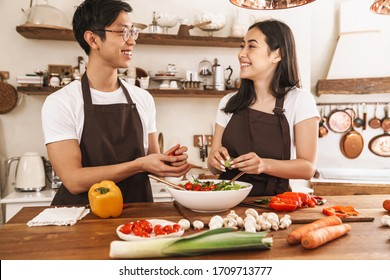 Image of multicultural couple smiling and looking on you while cooking dinner in cozy kitchen