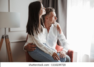 Image of multiethnic couple man and woman wearing casual clothing sitting together in armchair at hotel room and looking aside through window