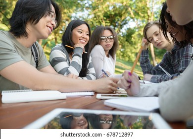 Image of multiethnic group of happy young students sitting and studying outdoors while talking. Looking aside.