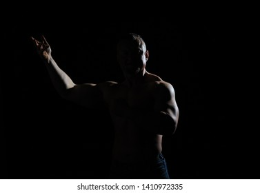 Image of muscle man posing in studio over black background