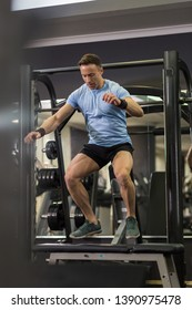 Image of a muscular man doing cardio exercises at the gym.