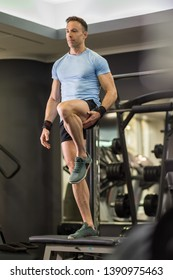 Image of a muscular man doing high knees exercises at the gym.