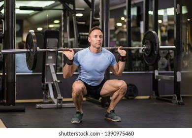 Image of a muscular man doing squads with heavy barbell at the gym.