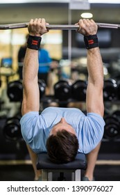 Image of a muscular man using barbell in exercise at the gym.