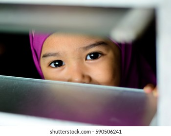 Image of a Muslim girl wearing hijab looking out the window