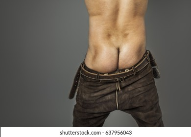 An image of a naked ass in bavarian leather pants