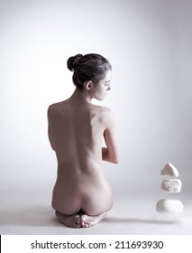 Image of naked female yogi mentally moving stones