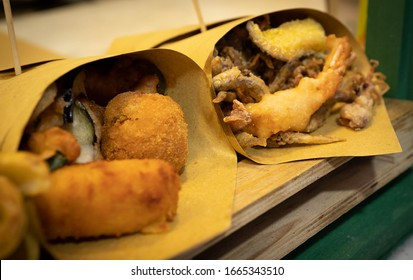 Image of naples street food - fried seafood, vegetables, cheese balls, potatoes folded in paper bags