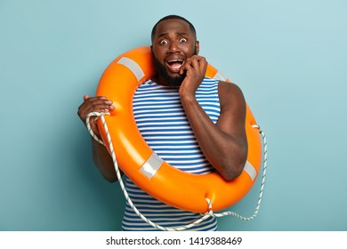 Image of nervous scared man trembles from fear, afraids of swimming without instructor, uses life saving equipment, wears sailor vest, poses over blue background. Athletic frustrated swimmer coach