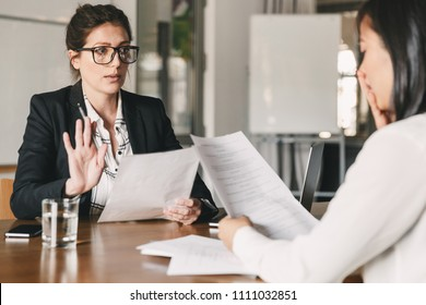 Image of nervous unsure asian woman talking and negotiating with businesswoman while sitting at table in office during job interview - business, career and recruitment concept