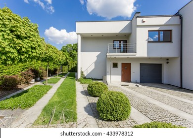 Image of new style white villa with lawn and stone driveway