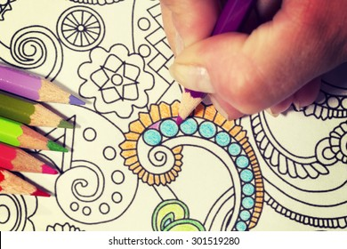 An image of a new trendy thing called adults coloring book with a vintage twist. In this image a person is coloring an illustrative and detailed pattern for stress relieve for adults.