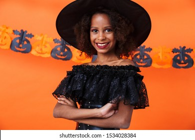 Image of nice african american girl in black halloween costume looking at camera and smiling isolated over orange pumpkin wall