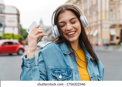 Image of nice laughing woman listening music with smartphone and wireless headphones on city street