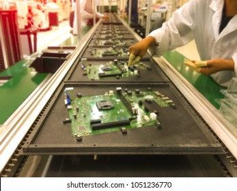 image not clear of Electronics manufacturing manual insertion of electronic components on printing circuit board assembly before wave soldering. in a electronic production,blurred background