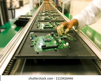 image not focus of hands manual insertion of electronic components on printing circuit board assembly before wave soldering. in a electronic production plat on a conveyor belt.,blurred background