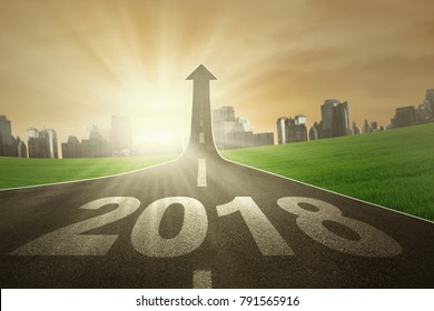 Image of numbers 2018 and upward arrow on the end of road. Symbolizing better future