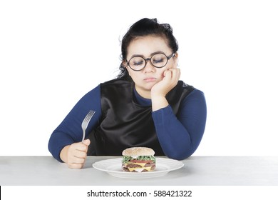 Image of obese female holds fork and hesitate to eat cheese burger, isolated on white background