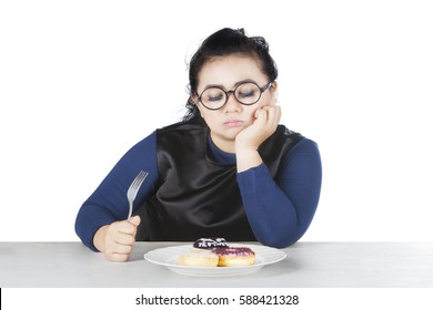 Image of obese female holds fork and hesitate to eat donuts, isolated on white background