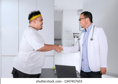 Image of obese man shaking hands with his doctor while visiting on the clinic
