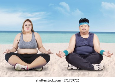 Image of obese young woman and her friend doing yoga on the beach
