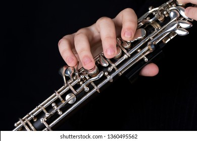 Image of an oboe on a black background. A woman plays the oboe with her hands.