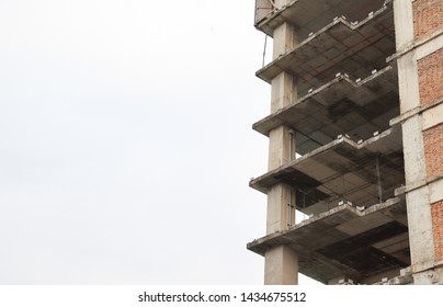 Image of old in-finished building with cloudy sky background. Unsafed contruction work in the city. Problem in developing country.