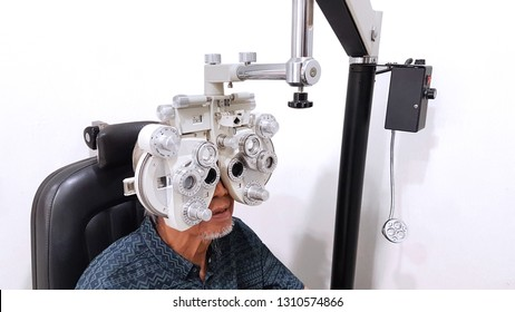 Image of old man doing eyes test by using phoropter in the hospital