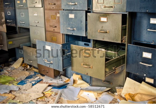 Image of old rusty filing cabinets in a derelict abandoned building with files scattered on the floor.