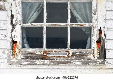 An image of an old weathered window with white peeling paint and rust.