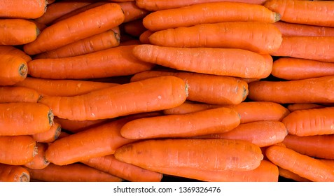 Image on pile of orange carrots in the market. pile of department store carrot. Pile of well cleaned beheaded-off raw carrot ready for customer to pick in retail supermarket.