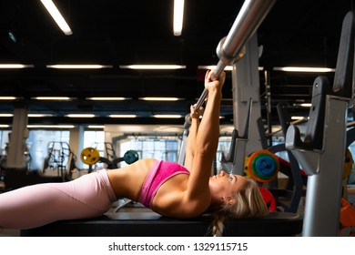 Image on side of sports blonde lying on bench with barbell.
