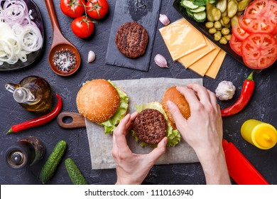 Image on top of two hamburgers, human hands and ingredients