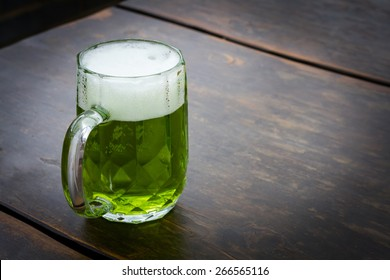 Image on an unusual green beer on wooden table. This beer is traditionally served on St. Patrick's day, but also during Easter time in Central Europe. It is lager mixed with extract from herbs.